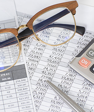 Documents spread out with a calculator and glasses